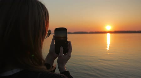 algılayıcı : girl is taking pictures of amazing sunset and river on embankment by her modern mobile phone