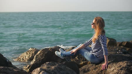 moloz : smiling blonde girl is resting, sitting on a big stones near sea in sunny day