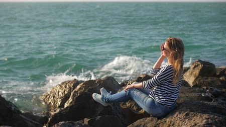 глыба : young woman is sitting alone on a cliff and admiring seascape in sunny summer day Стоковые видеозаписи