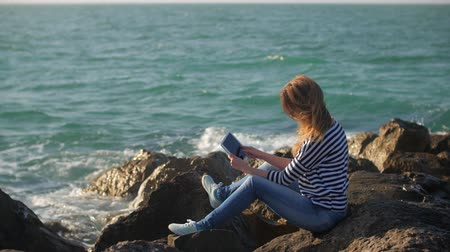 dalgakıran : teenage girl is using tablet with wireless internet, sitting on a breakwater in sunny day Stok Video