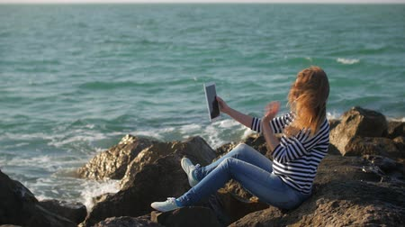 groyne : pretty woman is taking selfies, using camera of modern tablet, sitting on a stones near sea