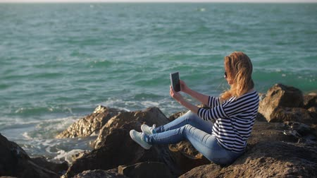 глыба : blonde girl with tablet in hands is sitting on a huge stones shore in sunny summer day Стоковые видеозаписи