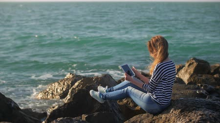 глыба : female student is relaxing on a seashore, and watching pictures in her tablet