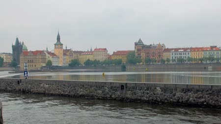 shores : vivid traditional buildings in Prague, water of Vltava river in foreground Stock Footage