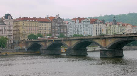 shores : tram is going over old bridge in Prague in cloudy day
