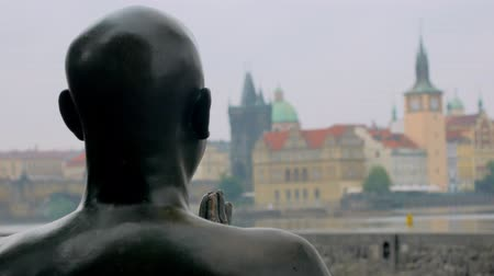 csehország : view from back of metal statue of human, looking on old traditional buildings in Prague Stock mozgókép
