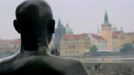 shores : statue of human praying with folded hands and looking on Prague view