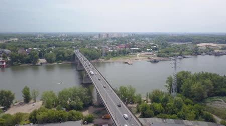 surroundings : cars are moving over modern bridge through river in summer day, aerial view