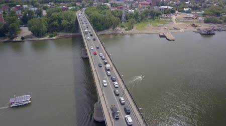 surroundings : drone is flying over river with bridge with moving cars in summer day