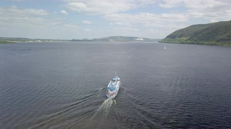 pleasure boats : aerial view of moving motor ship on wide river in sunny day, following boat