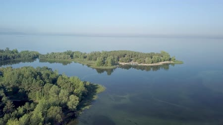 calm amazing aerial top view on landscape with wide river and small islands, covered forest