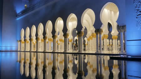 grand mosque : ABU DHABI, U.A.E. - JAN, 2018: Sheikh Zayed Grand Mosque, gallery with walking people and reflection in a fountain in night time