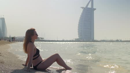 young blonde woman is wearing black bikini is sitting on a sandy beach in Dubai Стоковые видеозаписи
