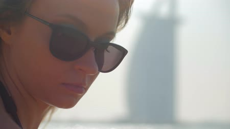 sensual young girl with sunglasses is resting on a city public beach in Dubai, close-up