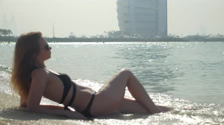 sexual young woman is wearing bikini is lying on a public beach in Dubai