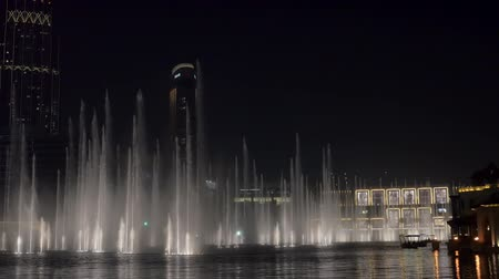 largest city : DUBAI, U.A.E. - JAN, 2018: large water streams of show of dancing fountains in night time near modern buildings Stock Footage