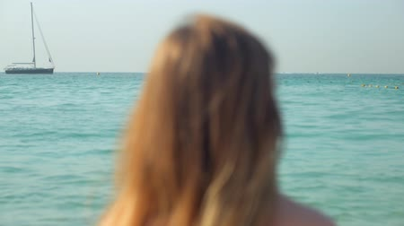 lonely romantic blonde woman is watching horizon on sea in sunny day