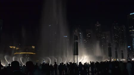 khalifa : DUBAI, U.A.E. - JAN, 2018: tourists are watching amazing show of large dancing fountains in night