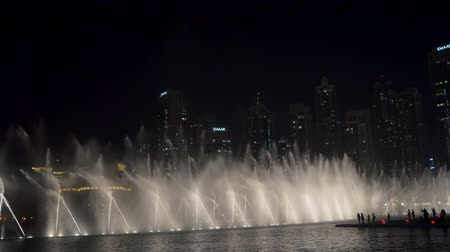 spraying : DUBAI, U.A.E. - JAN, 2018: water flows of spectacular show of large fountains in night time, unique performance Stock Footage
