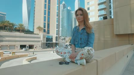 young beautiful blonde girl is sitting outdoors in Dubai Marina in sunny day Стоковые видеозаписи