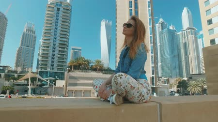 charming blonde girl is sitting outdoors in Dubai Marina in sunny day Стоковые видеозаписи