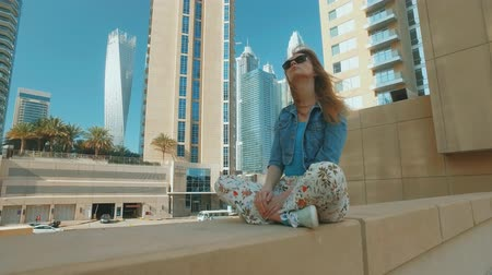 pensive blonde woman is sitting outdoors in Dubai Marina in sunny day Стоковые видеозаписи