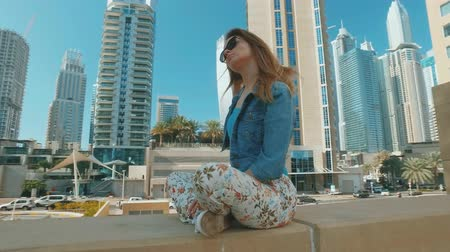 inspired blonde woman is sitting, crossed legs, outdoors in Dubai Marina in sunny day