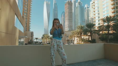 young tourist girl is taking selfies by smartphone, outdoors in Dubai Marina in sunny day Стоковые видеозаписи