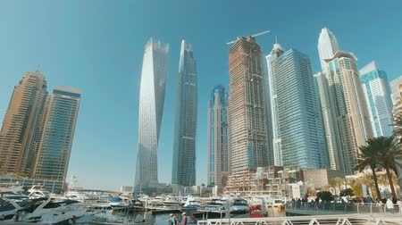 yacht mooring pier in Dubai Marina and skyscrapers in sunny day