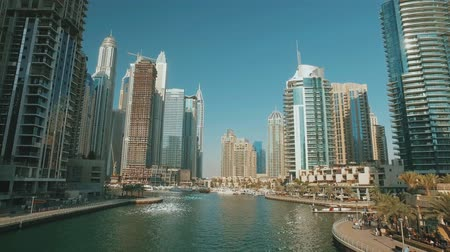 moving panorama from bridge in Dubai Marina in sunny day, reflection from water
