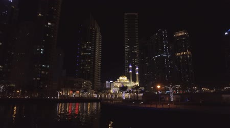 night view on magnificent small mosque in Dubai Marina, view from floating pleasure boat