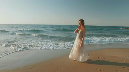 lonely blonde girl is walking alone on sandy beach in summer day, holding her hair Стоковые видеозаписи