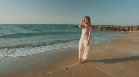 romantic blonde girl is walking alone on sandy beach in summer day, moving shot Стоковые видеозаписи