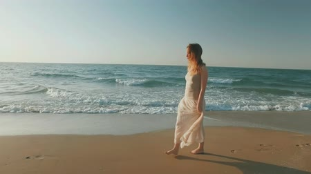 confident blonde woman is walking alone on seashore in summer day, lookingin distance Стоковые видеозаписи