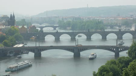 famous Charles bridge in Prague and other bridges over Vltava river, city life with tourists