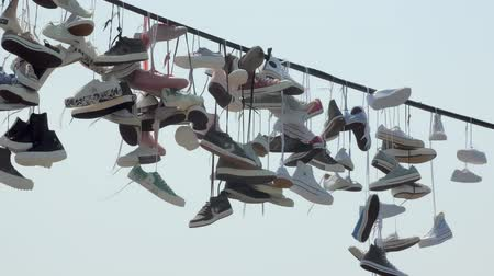 many of trendy sneakers are hanging on ropes outdoors, tilt up view against sky