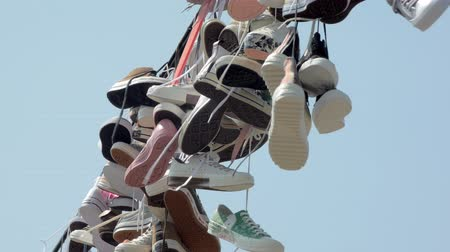 close-up view of shoefiti in city against clear blue sky, lace are swaying by wind in summer day