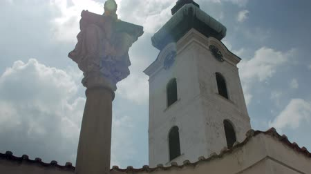 soška : panoramic tilt up view on tower and statue of Christ against cloudy sky and sun