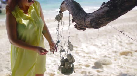uzun : A young girl in a yellow dress touches a white coral hanging on a rope on a beach on the island