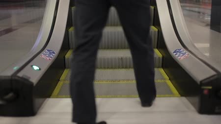 Two men climb the escalator. Legs