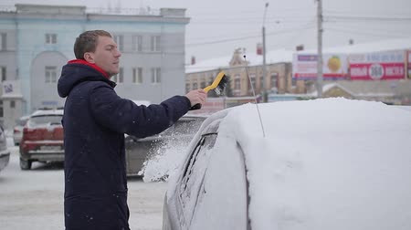 man cleans the car from snow with a brush Stock mozgókép