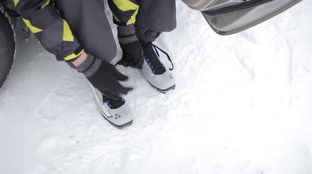 fisher : a man ties up his shoelaces on ski boots