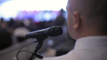 Businessman speaks into a microphone at a conference