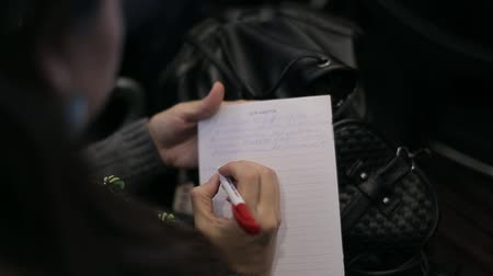 Women writes in a notebook at a conference Stock mozgókép