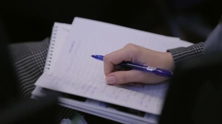 Woman takes notes in a notebook at a conference or training