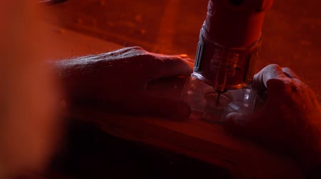 A man carves a figure with a jigsaw inside future wooden furniture with red light