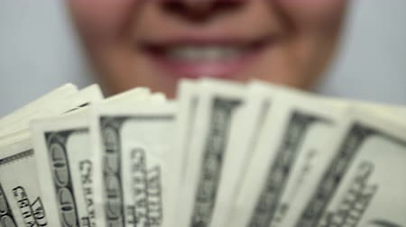 possession : Smiling girl on background of dollars. Pleasure, joy. Close-up