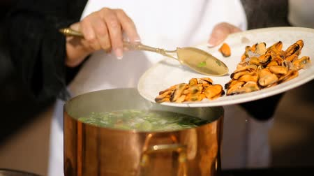scallop : the woman cook throws the mussels into the pan. cooking soup from mussels