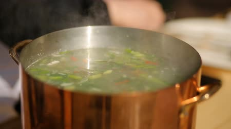 wok food : stirring with a spoon of soup from the mussels. Cooking process. close-up