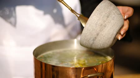 ebulição : stirring with a spoon of soup from the mussels. Cooking process. close-up
